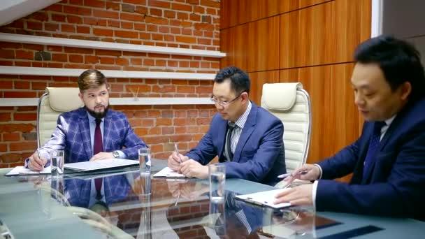 Tři vážné a sebevědomý podnikatelů během obchodních jednání v kanceláři