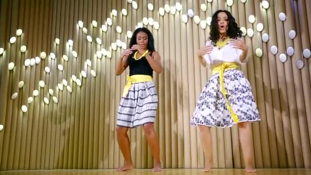 Two brunette mulatto girl are dancing on stage.