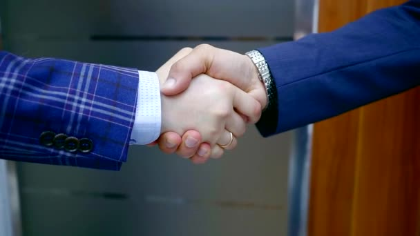 Close up shot of two successful and confident businessmen shaking hands after signing a deal.