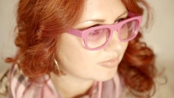 Közelről. egy fényes vörös haj, szemüveg rózsaszín keretek középkorú nő portréja
