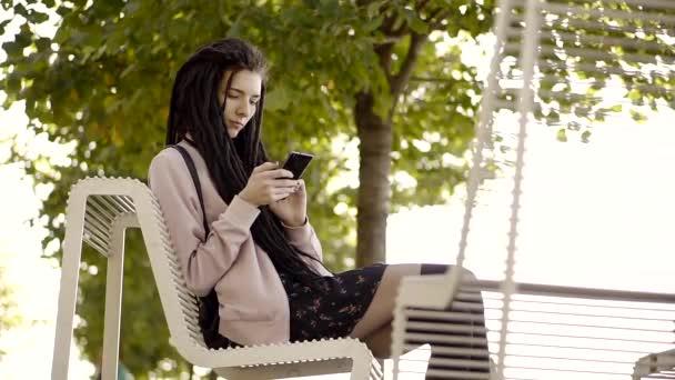 Frau mit apps auf Ihrem Smartphone den Text auf Ihrem Handy. Junge Frau mit Smartphone im City Park, Steadicam erschossen