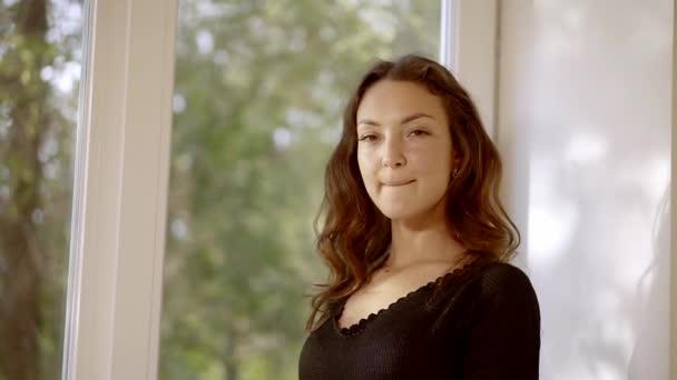 osamělý bruneta žena stojí u okna ve světlé místnosti. Denní světlo z okna