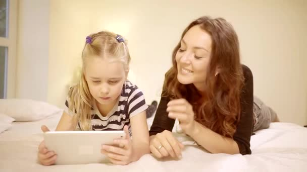 Beautiful Mother and Her Little Daughter Have Good Time Reading Childrens Books on a Tablet Computer.