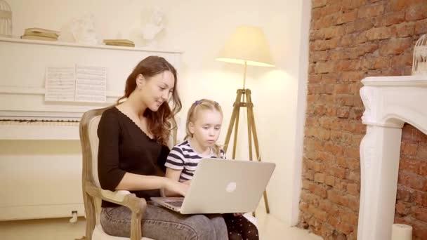 Giovane madre sta giocando sul portatile con mia figlia dolce tra le mie braccia. Camera con interni in stile classico e un pianoforte in sottofondo. rallentatore