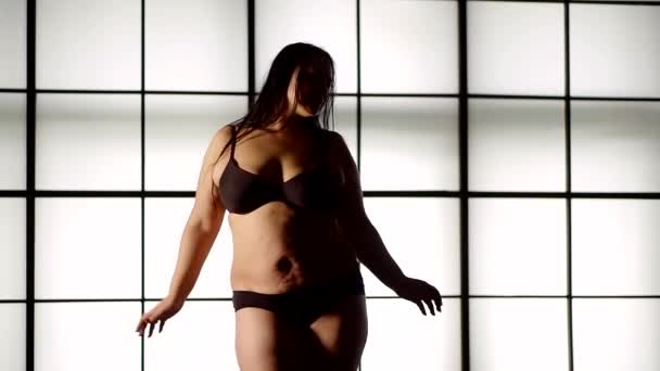 woman with a pronounced obesity dances cheerfully against a white large window. shakes fat belly cellulite