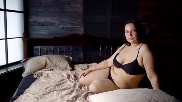 358c1a077ad6 Sexy gorda con obesidad está sentado en la cama en una habitación oscura.  Celulitis y los pliegues grasa