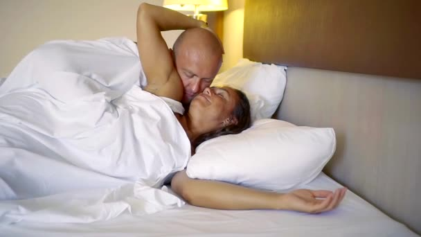man awakens his beloved woman in the morning in bed with gentle kisses. honeymoon couple middle-aged