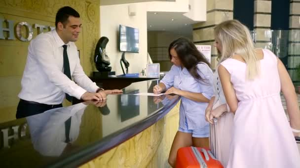 At the reception, a group of women with a suitcase happily meets the hotel staff. The staff cordially talks to the visitor with their Luggage when they arrive at the hotel.