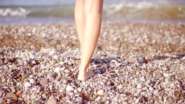 Zblízka. Žena vstoupí moře, na oblázkové pláži