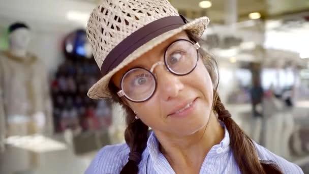 5d6cad6707 Portrait d'une femme d'âge mûr avec des lunettes rondes et un chapeau de  paille. couchait et faire des grimaces à la caméra– séquence vidéo