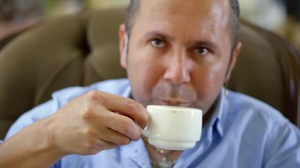 man with a beard drinks morning coffee from a white mug and puts it on a saucer on the table