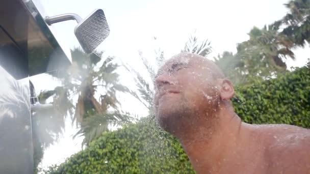 Glatzkopf großer muskulöser Mann unter der Dusche in einem tropischen Park