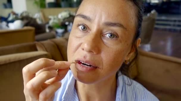 portrait close-up of a middle-aged woman with wrinkles on her face with pleasure eating a sprig of red currant