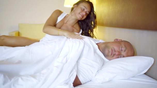 morning at the hotel. a woman will sleep her man lying in bed