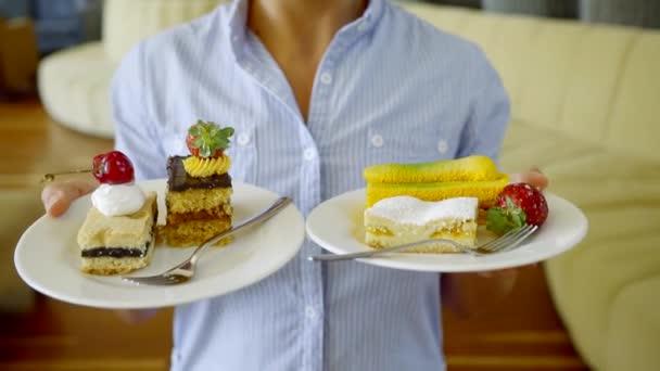 Vista del primo piano di bella cupcake su un piattino. La donna tiene un piatto con la torta