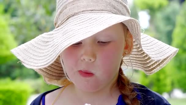 Girl holds ice cream cone in front of face before eating in summertime scene