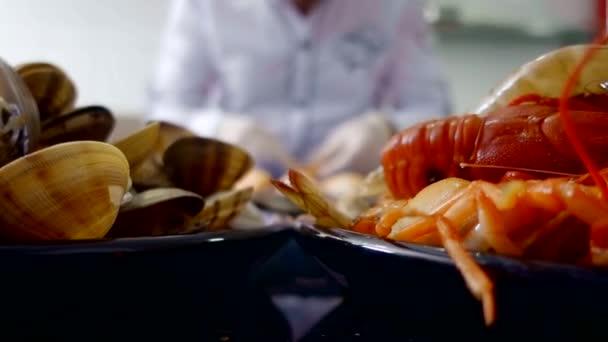 Šéfkuchař připravuje rybí pokrmy. krevety, mušle a raků. Asijské kuchyně
