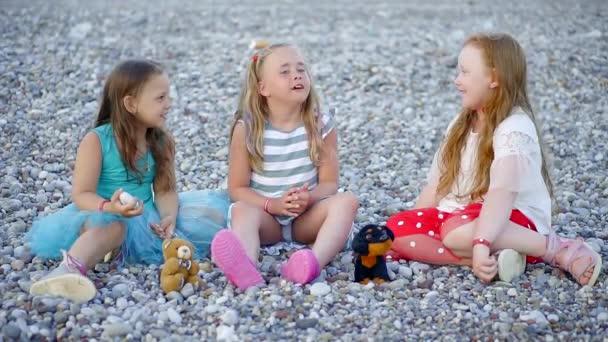 malé vtipné dívky hrát s plyšovou hračku na skalnaté pláži v létě