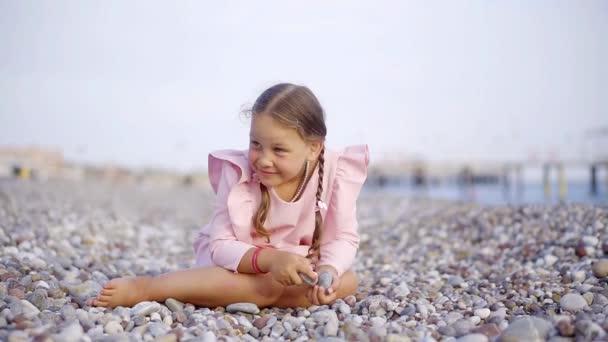 Een leuke en grappige meisje zit op een stenige strand en