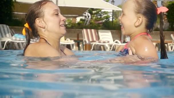 Žena a její dcera jsou blbnout v bazénu, Máma a dítě se směje
