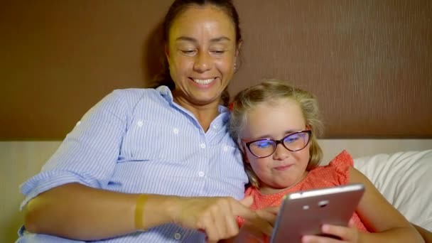 adult woman is hugging her little daughter, leaning on a headboard of a bed, watching video on a tablet