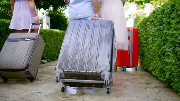 ženské jsou pěší a nošení kufrů ve dvoře hotelu v letním dni, zadní pohled na ženy
