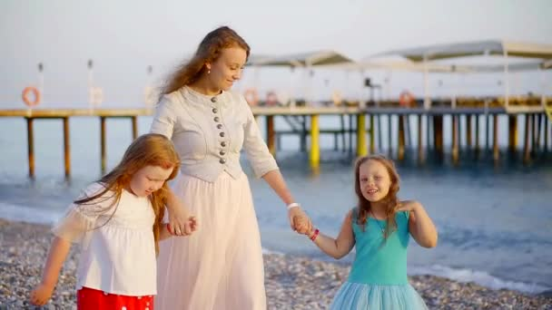 young mother is walking over sea beach with her two cute daughters, chatting and enjoying in sunset time