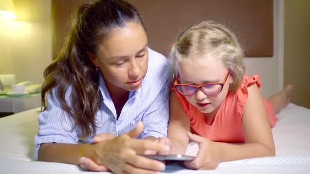 felnőtt nő az ágyon a hálószobában közelében kis lánya, videojátékok által tabletta az esti órákban
