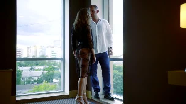 je silný svalnatý muž objímá svou přítelkyni, obě stojí proti velká okna v místnosti