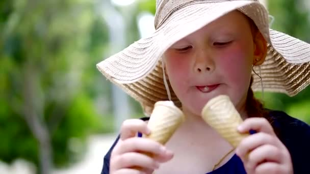 little girl is wearing big summer hat is eating two ice cream in waffles, walking outdoors, close-up