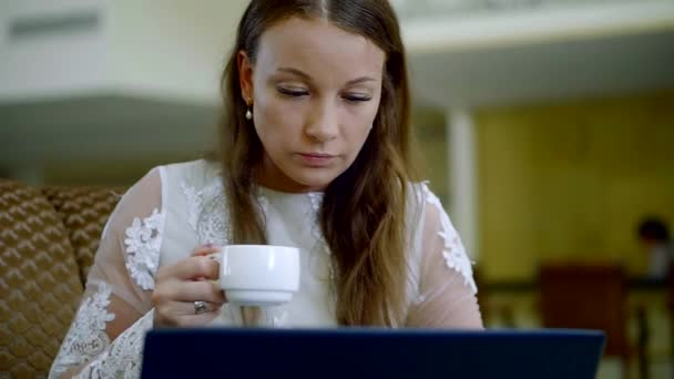 adult brown-haired woman is working with laptop, browsing and surfing the internet, drinking coffee