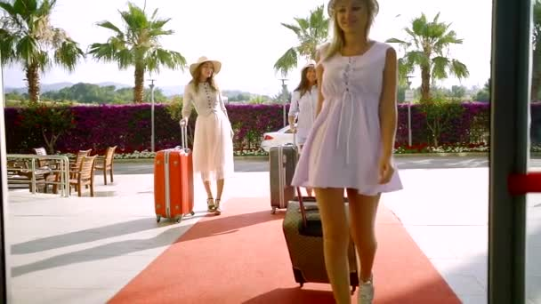 Three beautiful adult women arrive in a hotel with a suitcases.