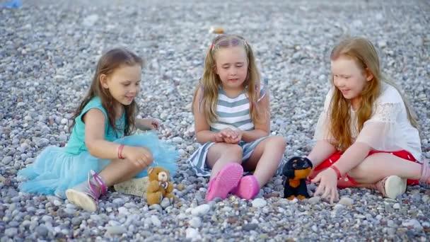 Tři šťastné děti mluví a hraje na oblázkové pláži.