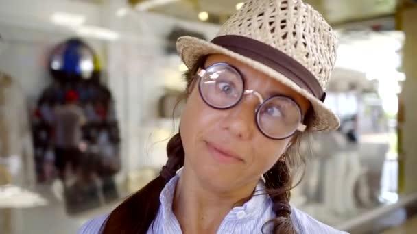 pro dospělé komické žena se šklebící a kroutit pro fotoaparát, oblečený kulatý legrační brýle, sečení oči, široce se usmívala