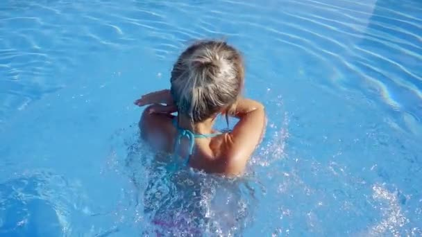 carefree young woman is whirling in swimming pool in sunny day on vacation, smiling broadly