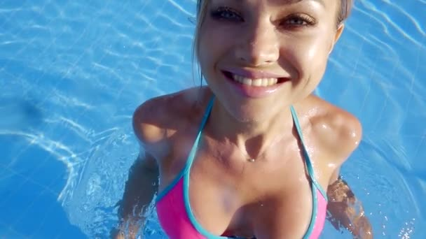 svůdná mladá blondýna skoky ve vodě bazénu, fotoaparát ukazuje její štíhlé sexy tělo pod vodou a nad