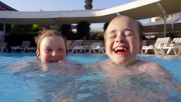 zwei glückliche kleine Mädchen schwimmen an einem sonnigen Sommertag im Pool und lachen breit lächelnd