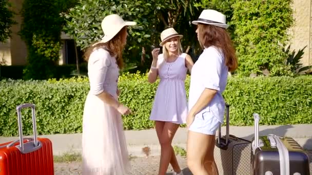 Charming and cheerful women in hats and light dresses having a conversation in city.