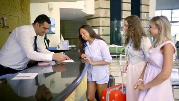 Tři krásné ženy check inu v hotelu letní. Žena turisté se zavazadly na hotelové recepci. Příjezd.