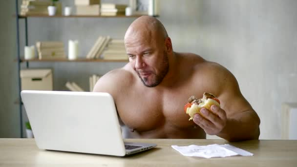 man eating harmful fast food and watching a video about the benefits of healthy eating on a laptop