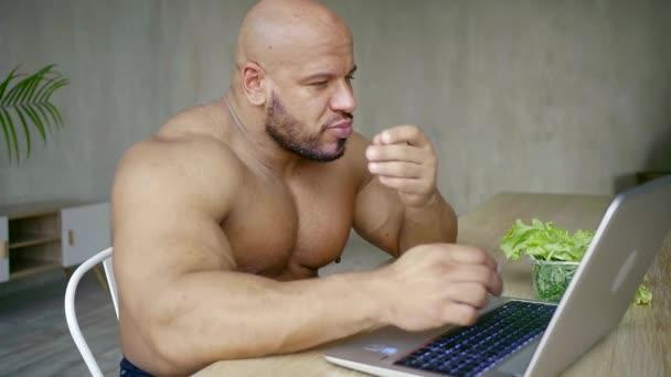 Portrét muže, který komunikuje s přáteli v sociálních sítích v přenosném počítači a jí zelený salát