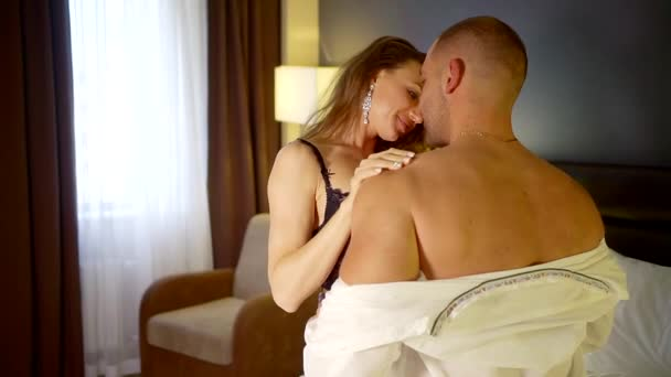Sexy and sensual woman gently touching mans naked body in bed.