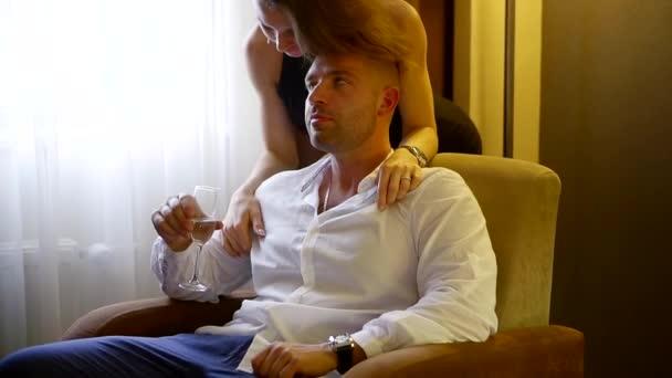 Krásný pár dostat intimní v hotelovém pokoji po nápoje