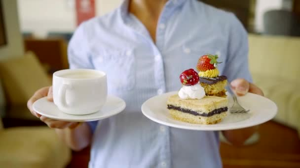 Close up shot of a woman holding two plates with dessert and cup of coffee for breakfast.