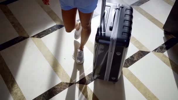 Shot from above of a female tourist going into hotel with a big black suitcase.