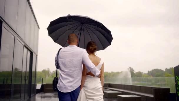 pár je chůze v letní déšť v denní, člověk je objímala svou přítelkyni a drží deštník