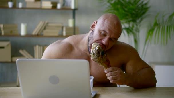 bulliger Mann beißt großen gebratenen Schinken auf einen Knochen und schaut auf das Display eines Laptops in einem Haus
