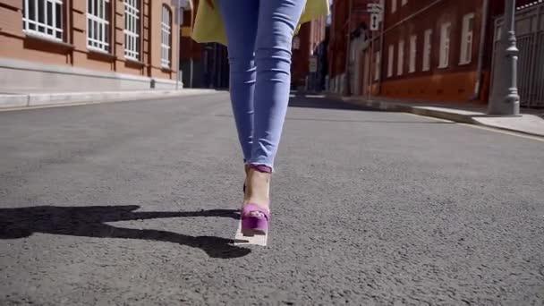 afrikanisches Mädchen in fliederfarbenen Stöckelschuhen, das mitten auf der Straße in der alten Straße läuft