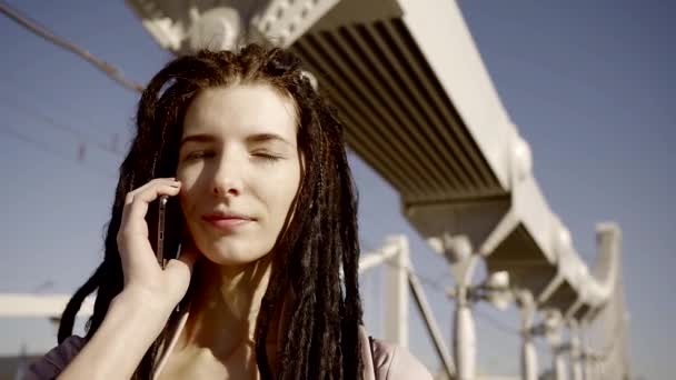 Amazing woman with dreadlocks is talking on the phone outdoor.