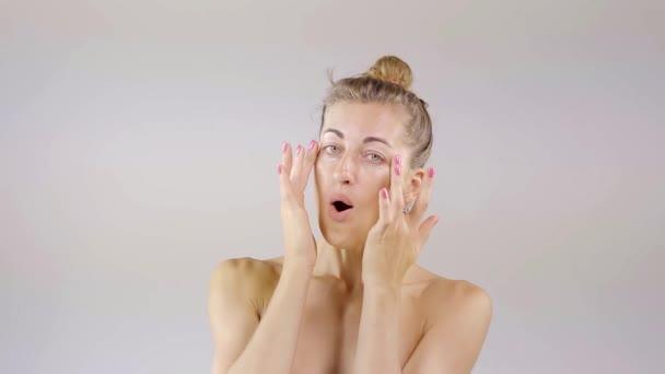 Mladá atraktivní žena smetany její obličej péče o pleť krémem a hloupé